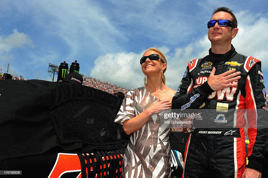 Kurt Busch, driver of the #78 Furniture Row/Sealy Chevrolet, and girlfriend Patricia Driscoll stand on the grid during pre-race ceremonies for the NASCAR Sprint Cup Series Quicken Loans 400 at Michigan International Speedway on June 16, 2013 in Brooklyn, Michigan.