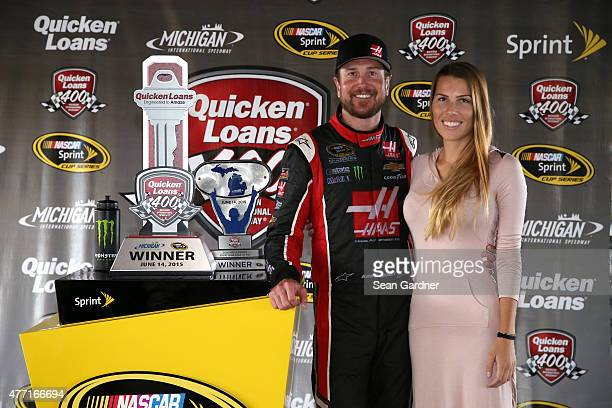 Kurt Busch driver of the Haas Automation Chevrolet and his girlfriend Ashley Van Metre celebrate in an alternate Victory Lane after winning the...