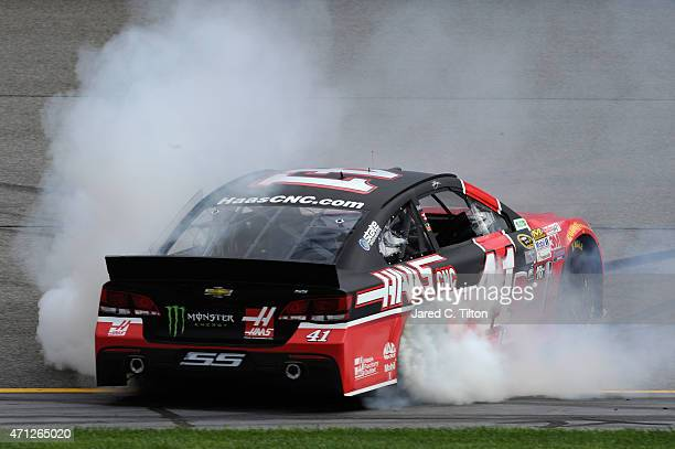 Kurt Busch driver of the Haas Automation Chevrolet celebrates with a burnout after winning the NASCAR Sprint Cup Series Toyota Owners 400 at Richmond...