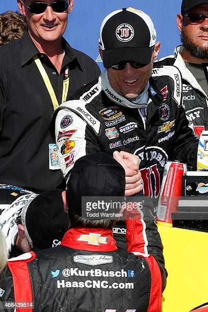 Kurt Busch driver of the Haas Automation Chevrolet congratulates Kevin Harvick driver of the Jimmy John's/ Budweiser Chevrolet in Victory Lane after...