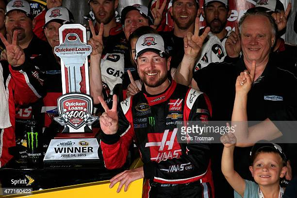 Kurt Busch, driver of the Haas Automation Chevrolet, Gene Haas, co-owner of Stewart Haas Racing, and his team pose in an alternate Victory Lane after...