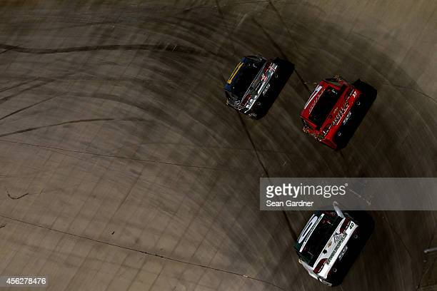 Kurt Busch driver of the Haas Automation Chevrolet leads Mike Bliss driver of the Accell Construction Inc and Landon Cassill driver of the Newtown...
