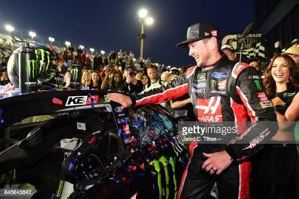 Kurt Busch driver of the Haas Automation/Monster Energy Ford affixes the winner's decal to his car in Victory Lane after winning the 59th Annual...