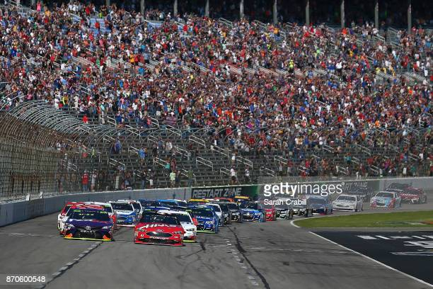 Kurt Busch driver of the Haas Automation/Monster Energy Ford and Denny Hamlin driver of the FedEx Office Toyota lead the field past the green flag to...