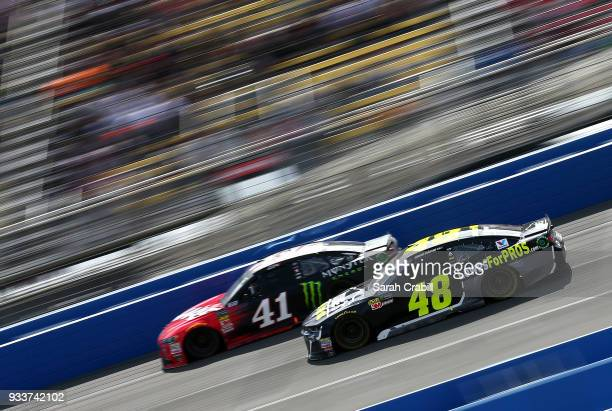 Kurt Busch driver of the Haas Automation/Monster Energy Ford leads Jimmie Johnson driver of the Lowe's for Pros Chevrolet during the Monster Energy...