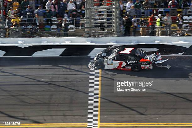 Kurt Busch driver of the HendrickCarscom Chevrolet drives across the finish line under caution after being involved in an on track incident during...
