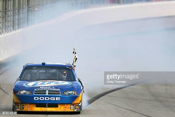 Kurt Busch, driver of the Miller Lite Dodge, does a burnout after winning the NASCAR Sprint Cup Series Kobalt Tools 500 at Atlanta Motor Speedway on...
