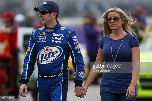 Kurt Busch driver of the Miller Lite Dodge walks down pit road with wife Eva during qualifying for the NASCAR Sprint Cup Series LENOX Industrial...