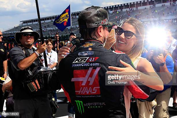 Kurt Busch driver of the Monster Energy/Haas Automation Chevrolet and his girlfriend Ashley Van Metre celebrate in Victory Lane after winning the...