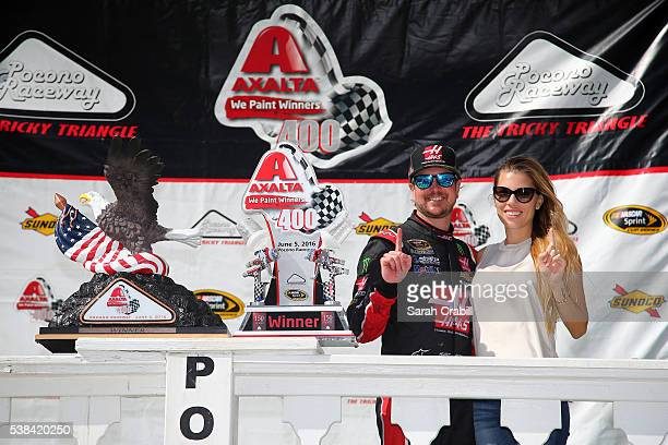 Kurt Busch, driver of the Monster Energy/Haas Automation Chevrolet, and his girlfriend Ashley Van Metre pose in Victory Lane after winning the NASCAR...