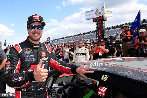 Kurt Busch driver of the Monster Energy/Haas Automation Chevrolet poses with the winner's decal on his car in Victory Lane after winning the NASCAR...