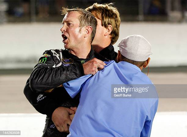 Kurt Busch driver of the Phoenix Construction Services Chevrolet is held back during scuffle with Ryan Newman driver of the Wix Filters Chevrolet...