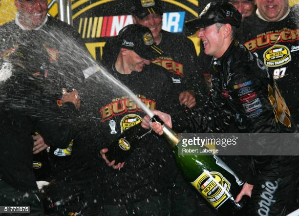 Kurt Busch driver of the Roush Racing Sharpie Ford sprays his team members with champagne after winning the NASCAR Nextel Cup Series Championship at...