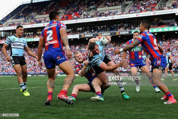 Kurt Capewell of the Sharks is tackled by the Knights defence during the round 26 NRL match between the Newcastle Knights and the Cronulla Sharks at...