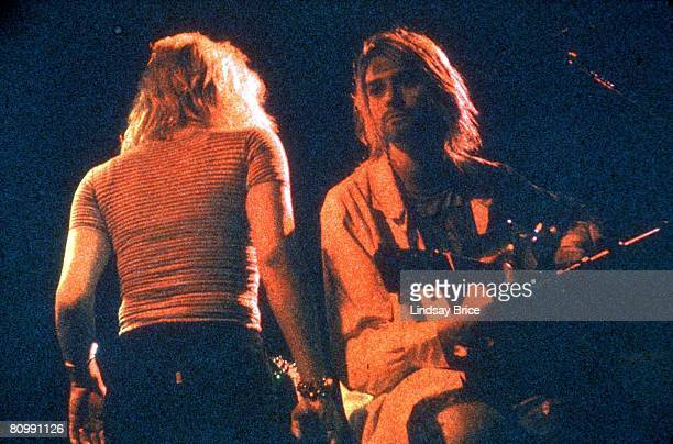 Kurt Cobain a symbolic BandAid on his forehead seated onstage with acoustic guitar looks into the distance as Courtney Love passes behind him during...