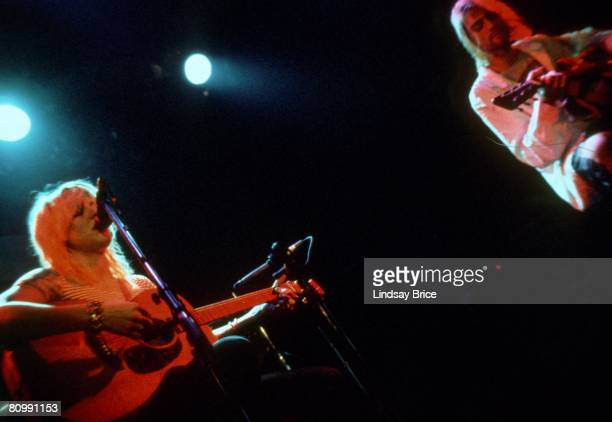 Kurt Cobain and Courtney Love both on acoustic guitar confer between songs as they perform together for Rock for Rape benefit at Club Lingerie in...