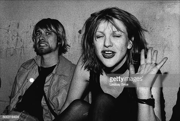 Kurt Cobain and Courtney Love pose for photograph, Kurt grimacing for the camera and Courtney waving, on VIP balcony during Mudhoney concert at the...