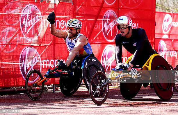 Kurt Fearnley of Australia celebrates victory as he crosses the finish line ahead of Marcel Hug of Switzerland to win the Mens Elite Wheelchair...