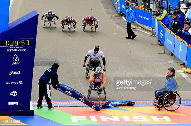 Kurt Fearnley of Australia crosses the finish line to win the Pro Pushrim Men's division followed by second place Ernst Van Dyk of South Africa in...
