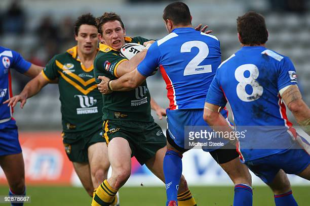 Kurt Gidley of Australia is held up by Dimitri Pelo of France during the Four Nations match between France and Australia at Stade Charlety on...