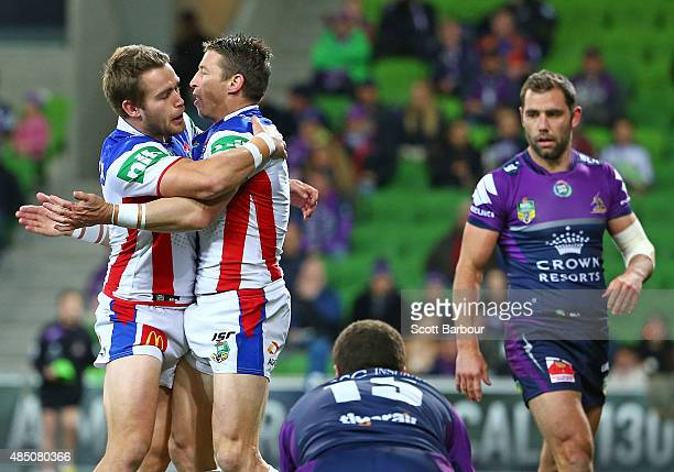Kurt Gidley of the Newcastle Knights is congratulated by his teammates after scoring a try as Cameron Smith of the Melbourne Storm looks on during...
