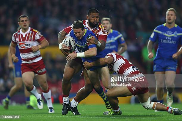 Kurt Gidley of Warrington is held up by FrankPaul Nuuausala and and Willy Isa of Wigan during the First Utility Super League Final between Warrington...