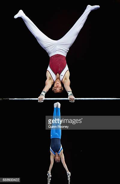 Kurt Grumelart of Queensland competes on the high bar as Alexander Waro of New South Wales competes on the parrallel bars during the 2016 Australian...