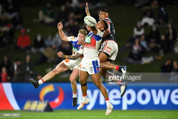Kurt Mann and Hymel Hunt of the Knights compete for the ball against Daniel Tupou of the Roosters during the round 19 NRL match between the Sydney...