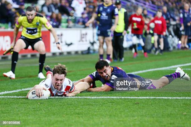 Kurt Mann of the Dragons scores a try past Jahrome Hughes of the Storm during the round 17 NRL match between the Melbourne Storm and the St George...