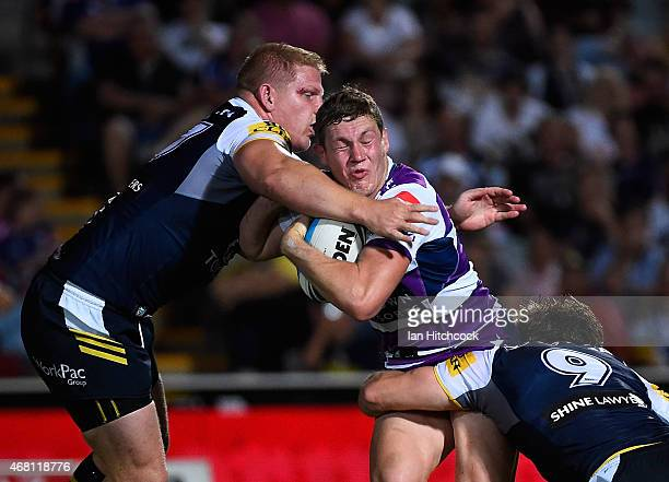 Kurt Mann of the Storm is tackled by Ben Hannant and Rory Kostjasyn of the Cowboys during the round four NRL match between the North Queensland...