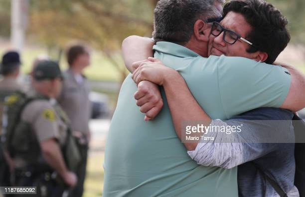 Kurt Rennels hugs his son Eric after reuniting at a park near Saugus High School after a shooting at the school left two students dead and three...