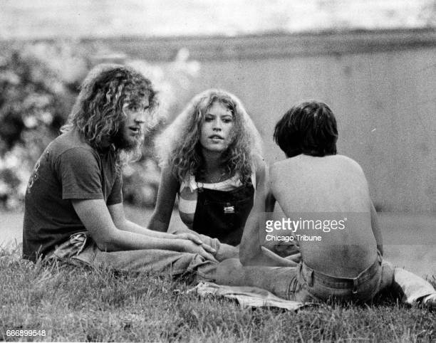 Kurt Rouse left and William Rouse right sons of slain Libertyville Ill couple Bruce and Darlene Rouse talk with a woman on the lawn of the family's...