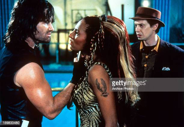 Kurt Russell pointing gun at Pam Grier while Steve Buscemi watches in a scene from the film 'Escape From L.A.', 1996.