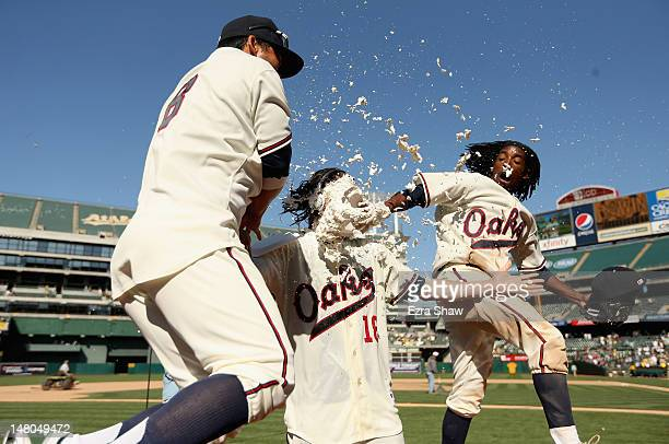 Kurt Suzuki and Jemile Weeks smash cream pies in face of Josh Reddick of the Oakland Athletics after he hit a double that scored Jemile Weeks of the...