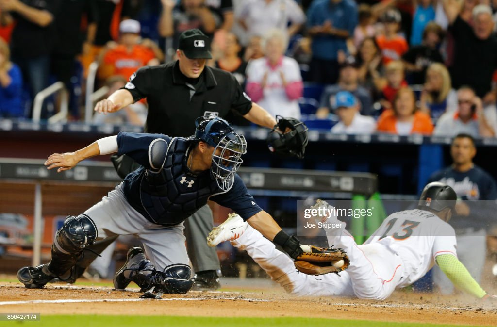 Kurt Suzuki #24 of the Atlanta Braves applies a late tag as Marcell Ozuna #13 of the Miami Marlins scores in the fifth inning at Marlins Park on October 1, 2017 in Miami, Florida.