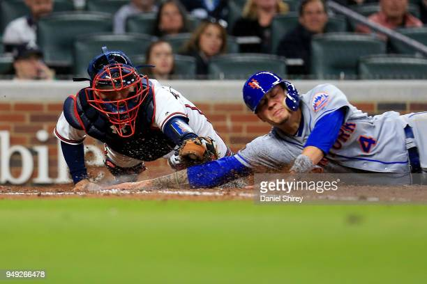 Kurt Suzuki of the Atlanta Braves dives to tag out Wilmer Flores of the New York Mets at home plate during the sixth inning against the New York Mets...