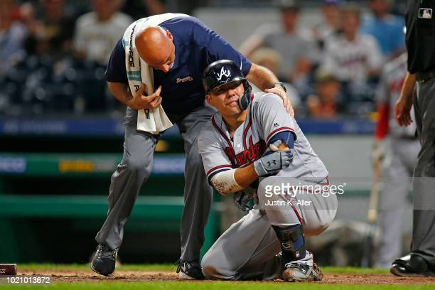 Kurt Suzuki of the Atlanta Braves grimaces after being hit by a pitch in the ninth inning against the Pittsburgh Pirates at PNC Park on August 21...