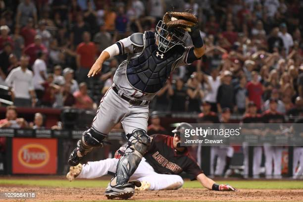 Kurt Suzuki of the Atlanta Braves makes the out on Nick Ahmed of the Arizona Diamondbacks in the tenth inning of the MLB game at Chase Field on...