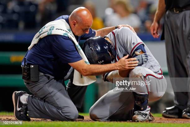 Kurt Suzuki of the Atlanta Braves reacts after being hit by a pitch in the ninth inning against the Pittsburgh Pirates at PNC Park on August 21 2018...