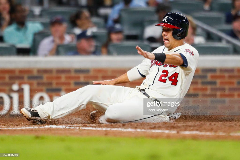 Kurt Suzuki #24 of the Atlanta Braves slides in to score in the fifth inning of an MLB game against the Miami Marlins at SunTrust Park on September 9, 2017 in Atlanta, Georgia. The Braves won 6-5.