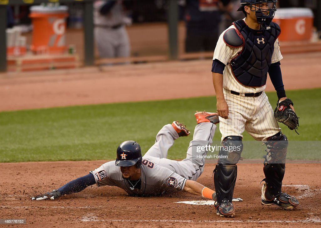 Kurt Suzuki #8 of the Minnesota Twins looks on as Carlos Gomez #30 of the Houston Astros slides safely into home plate to score during the fourth inning of the game on August 29, 2015 at Target Field in Minneapolis, Minnesota. The Astros defeated the Twins 4-1.