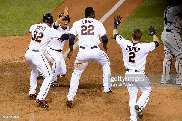 Kurt Suzuki of the Minnesota Twins slides into home plate to score the winning run as teammates Aaron Hicks Brian Dozier and Miguel Sano wait to...