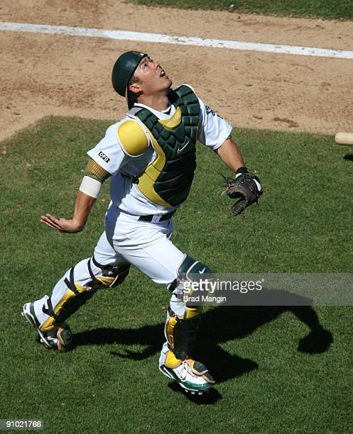 Kurt Suzuki of the Oakland Athletics chases a foul ball against the Cleveland Indians during the game at the OaklandAlameda County Coliseum on...