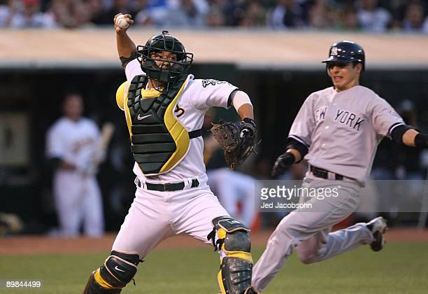 Kurt Suzuki of the Oakland Athletics throws to first base on a double play hit by Alex Rodrigues of the New York Yankees in the third inning during...
