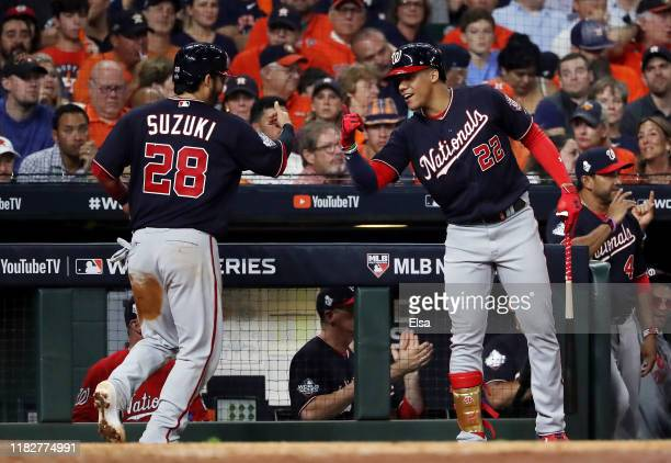 Kurt Suzuki of the Washington Nationals is congratulated by his teammate Juan Soto after scoring a run on a hit by Adam Eaton against the Houston...