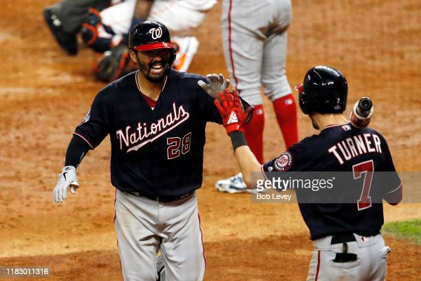 Kurt Suzuki of the Washington Nationals is congratulated by his teammate Trea Turner after hitting a solo home run against the Houston Astros during...