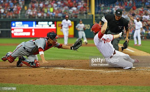 Kurt Suzuki of the Washington Nationals is unable to make the tag on Chase Utley of the Philadelphia Phillies as he scores a run in the fourth inning...