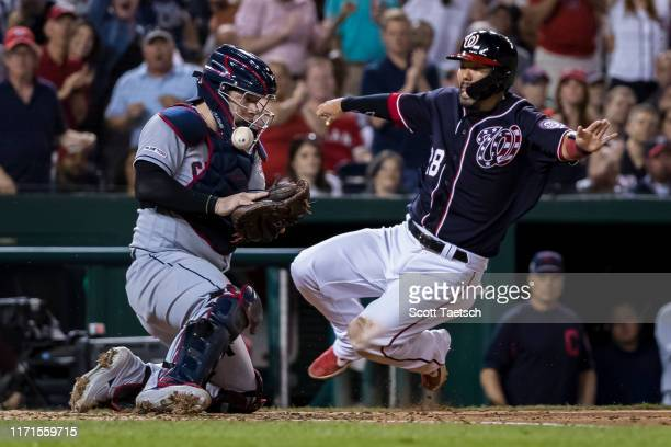 Kurt Suzuki of the Washington Nationals slides safely into home plate in front of Roberto Perez of the Cleveland Indians during the sixth inning at...