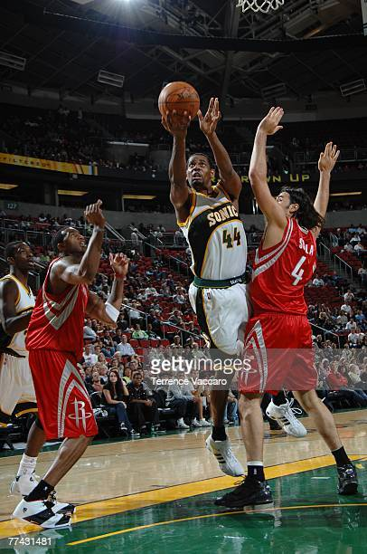 Kurt Thomas of the Seattle SuperSonics goes to the basket between the defense of Luis Scola and Tracy McGrady of the Houston Rockets in a preseason...