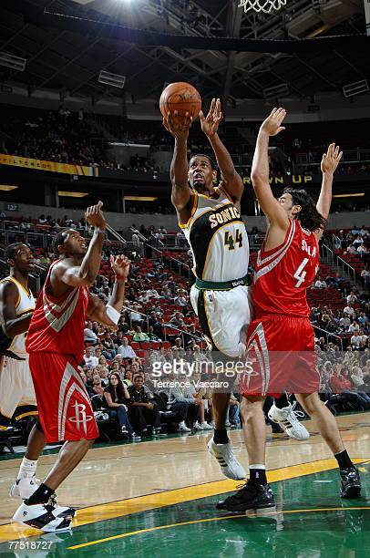 Kurt Thomas of the Seattle SuperSonics lays the ball up over Luis Scola and Tracy McGrady of the Houston Rockets during the game at Key Arena on...